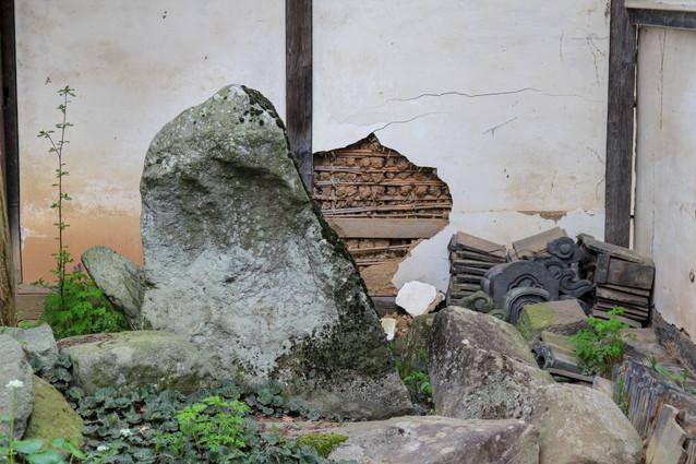 崩れた壁と庭石